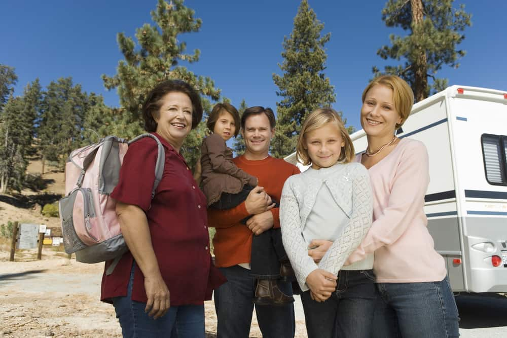 Mom, dad, toddler boy, girl and grandmother standing outside RV s