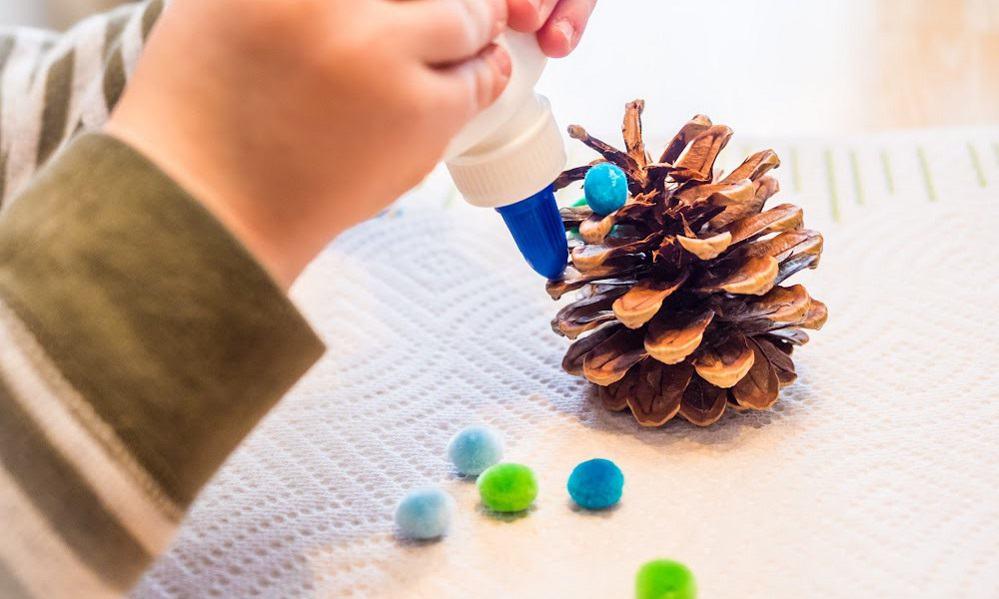 child hands making a pine cone ornament